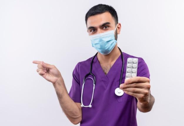 Jonge mannelijke arts draagt paarse chirurg kleding en stethoscoop medische masker stak pillen naar camera wijst naar kant op geïsoleerde witte muur