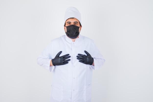 Jonge mannelijke arts hand in hand op de borst in wit uniform en ziet er zelfverzekerd uit, vooraanzicht.