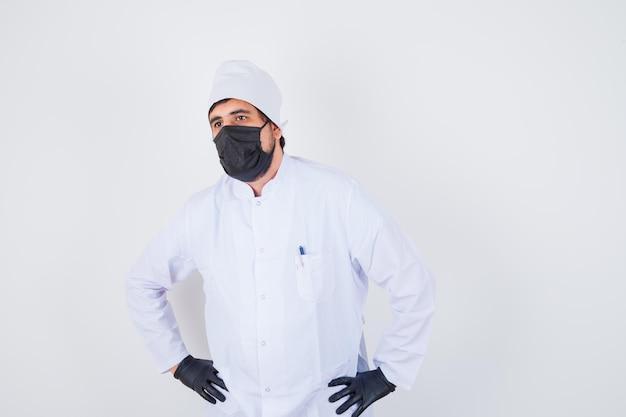 Jonge mannelijke arts hand in hand op taille in wit uniform en zelfverzekerd, vooraanzicht.