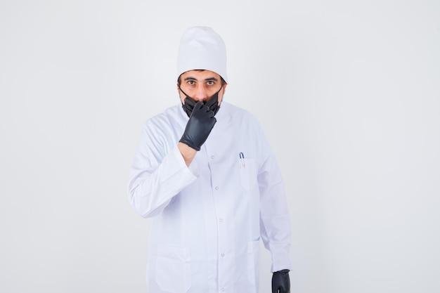 Jonge mannelijke arts in een wit uniform openingsmasker en er serieus uitziend, vooraanzicht.