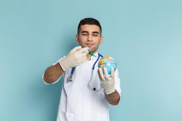 Jonge mannelijke arts in wit kostuum met de blauwe injectie van de stethoscoopholding