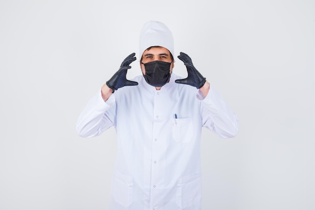 Jonge mannelijke arts in wit uniform die handen op een agressieve manier opheft en er geïrriteerd uitziet, vooraanzicht.