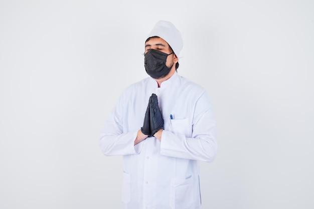 Jonge mannelijke arts in wit uniform die namaste-gebaar toont en er vredig uitziet, vooraanzicht.