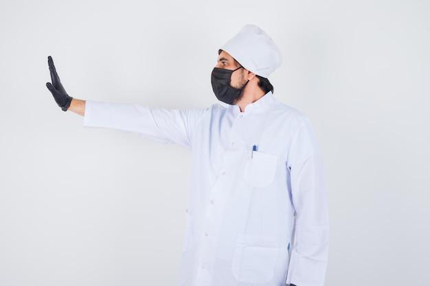 Jonge mannelijke arts in wit uniform met stopgebaar en zelfverzekerd, vooraanzicht.