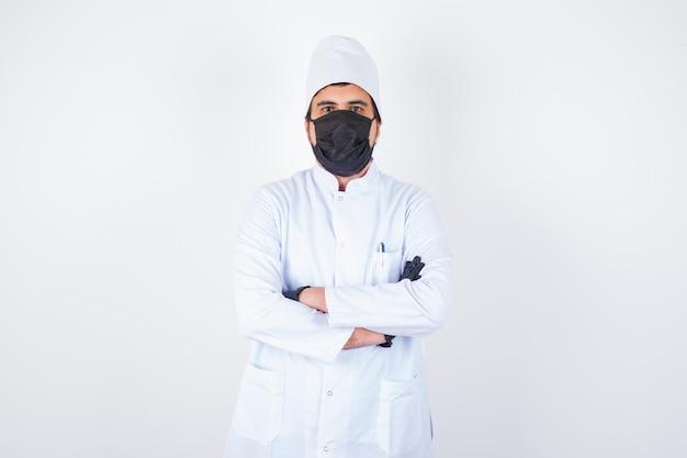 Jonge mannelijke arts in wit uniform staat met gekruiste armen en ziet er zelfverzekerd uit, vooraanzicht.