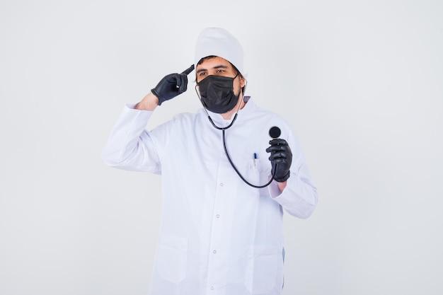 Jonge mannelijke arts in wit uniform wijzend hoofd terwijl hij een stethoscoop vasthoudt en er zelfverzekerd uitziet, vooraanzicht.