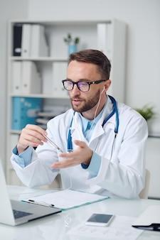 Jonge mannelijke arts in witte jas, bril en oortelefoon die medische aanbevelingen geeft aan online patiënt terwijl hij voor de laptop zit