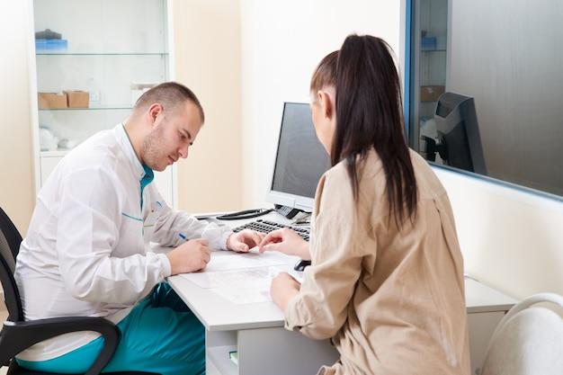 Jonge mannelijke arts onderzoekt en raadpleegt jonge vrouwelijke patiënt in de ziekenhuiskliniek. professioneel
