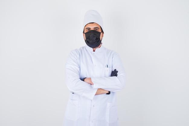 Jonge mannelijke arts staat met gekruiste armen in wit uniform en ziet er zelfverzekerd uit, vooraanzicht.