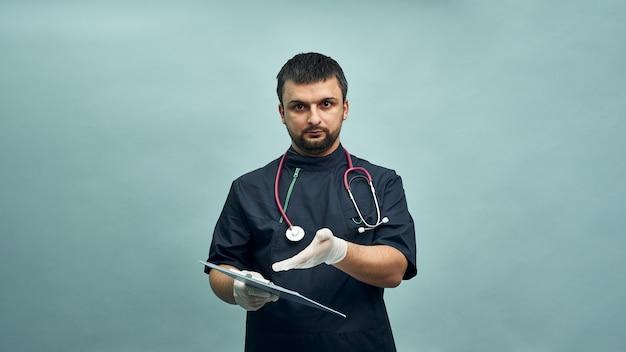 Jonge mannelijke arts wijst met zijn hand naar documenten op de tablet