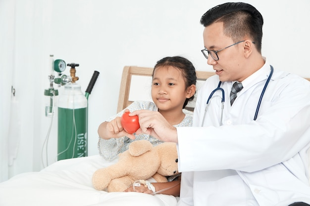 Jonge mannelijke artsenpediater die meisje controleren