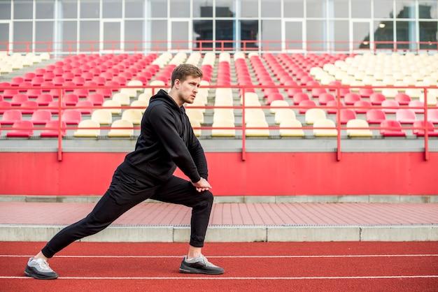 Jonge mannelijke atleet die in stadion opwarmen