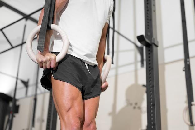 Jonge mannelijke atleet die traint met gymnastiekringen in de sportschool