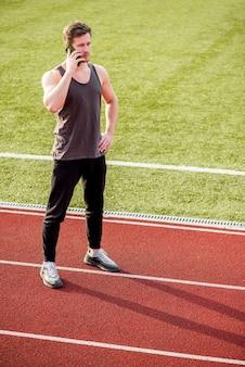 Jonge mannelijke atleet die zich op rasspoor bevindt dat op mobiele telefoon spreekt