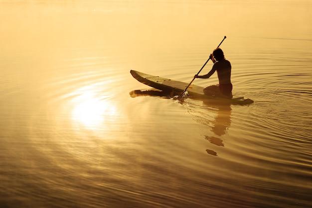 Jonge mannelijke atleet lange roeispaan in handen houden en 's ochtends op paddle board roeien.