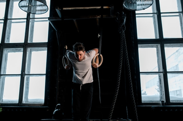 Jonge mannelijke atleet met gymnastiekringen in de sportschool focus op ringen van hoge kwaliteit foto