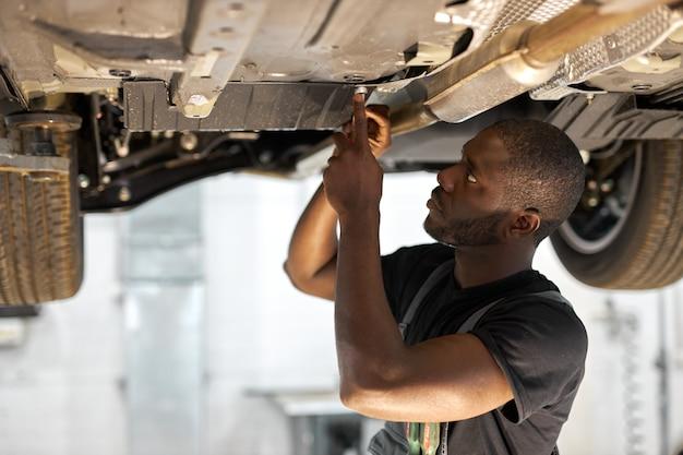 Jonge mannelijke automonteur in uniform auto in auto-service met opgeheven voertuig controleren