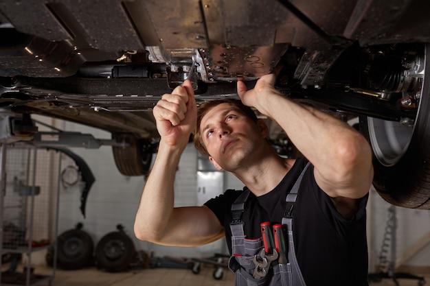 Jonge mannelijke automonteur in uniform controleren auto in auto-service