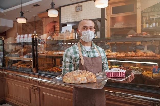 Jonge mannelijke bakker die medisch masker draagt dat brood en gebak verkoopt bij zijn bakkerijopslag