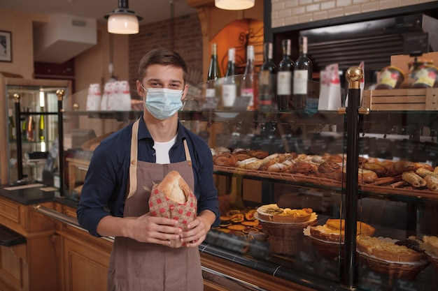 Jonge mannelijke bakker die medisch masker op het werk draagt tijdens coronavirus-pandemie