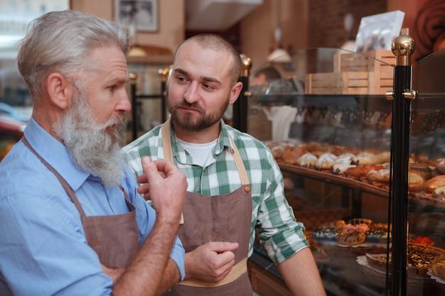 Jonge mannelijke bakker in gesprek met zijn bejaarde vader die bij hun familiebakkerij werkt