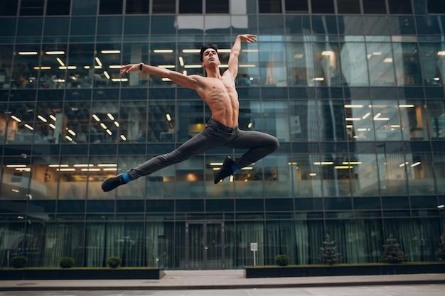 Jonge mannelijke balletdanser die op een gebouw springt. buitendans.