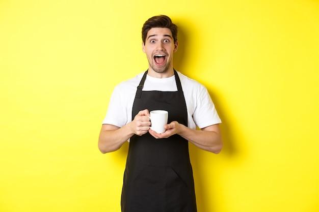 Jonge mannelijke barista die een koffiekopje vasthoudt en er verbaasd uitziet, staande in een zwarte schort tegen een gele achtergrond