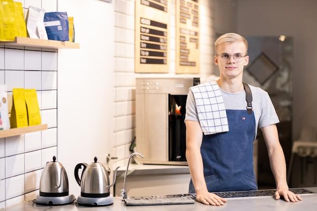 Jonge mannelijke barista in uniform op zoek naar jou terwijl je aan tafel staat met twee elektrische theepotten en koffiezetapparaat op de achtergrond