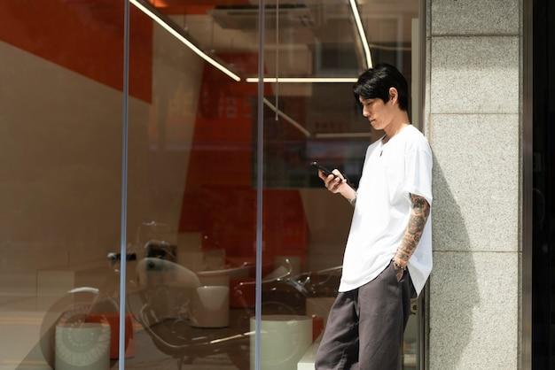 Jonge mannelijke barista met tatoeages die buiten het koffiehuis wachten voordat ze worden geopend