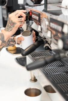 Jonge mannelijke barista met tatoeages die de koffiemachine gebruiken op het werk