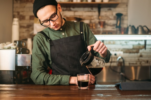 Jonge mannelijke barman giet koffie in een glas. koffiehuis op de achtergrond.