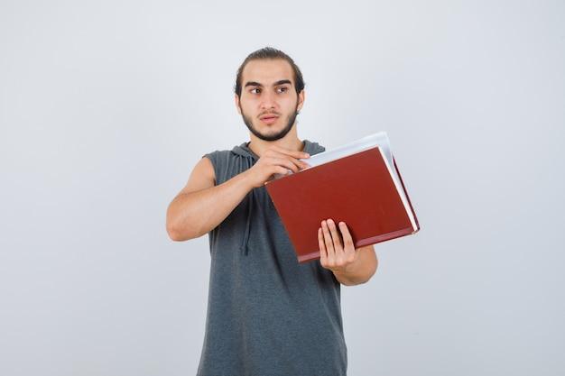 Jonge mannelijke bedrijf boek terwijl wegkijken in mouwloze hoodie en peinzend kijken. vooraanzicht.