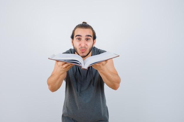 Jonge mannelijke bedrijf geopende boek in mouwloze hoodie en kijkt zelfverzekerd, vooraanzicht.