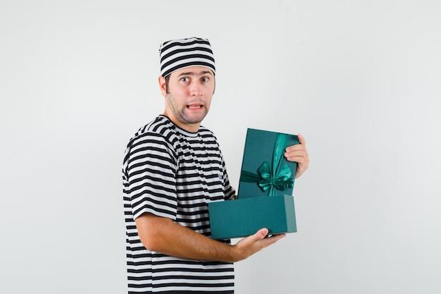 Jonge mannelijke bedrijf geopende geschenkdoos in t-shirt, hoed en op zoek verward.