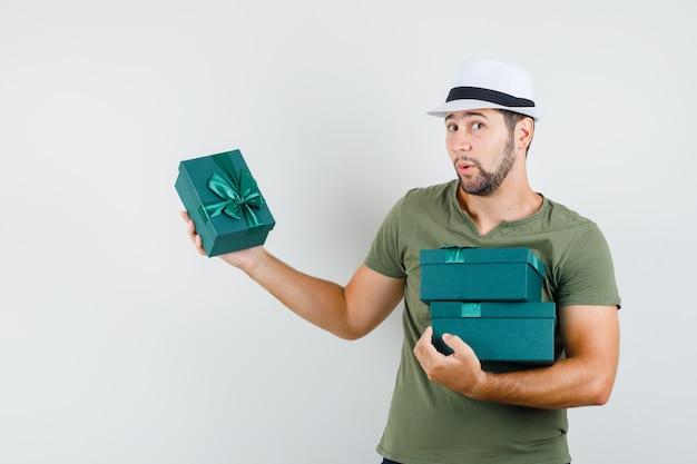 Jonge mannelijke bedrijf huidige dozen in groene t-shirt en hoed en peinzend kijken