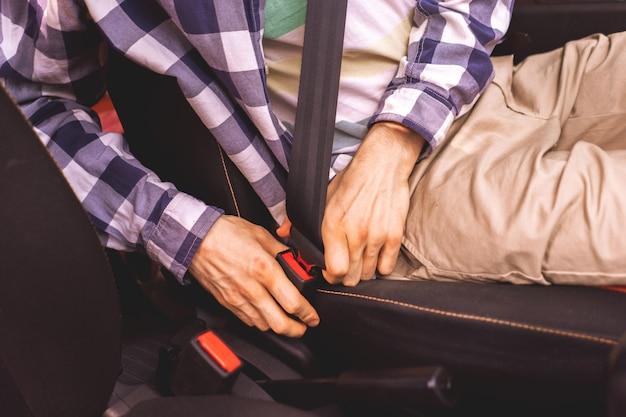 Jonge mannelijke bestuurder die de autogordel vastmaakt