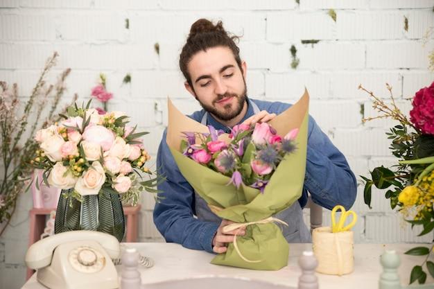 Jonge mannelijke bloemist die het bloemboeket in de bloemwinkel verpakken