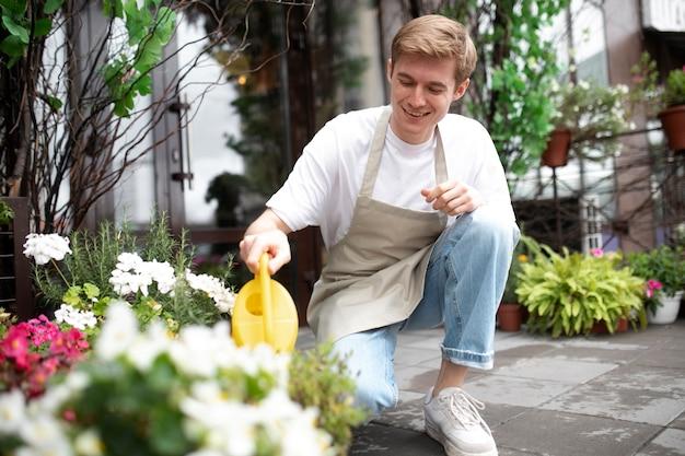 Jonge mannelijke bloemist die planten water geeft
