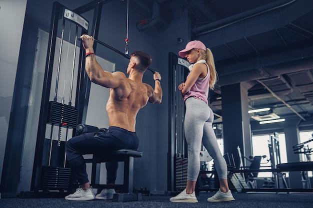 Jonge mannelijke bodybuilder die zware oefening doet terwijl zijn vriendin hem bekijkt