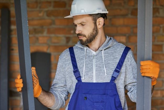 Jonge mannelijke bouwer die een overall en een helm draagt en er gefocust uitziet met metalen noppen voor gipsplaat