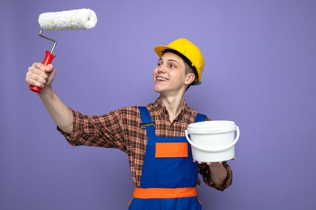 Jonge mannelijke bouwer die een uniforme emmer draagt en naar een rolborstel kijkt in zijn hand geïsoleerd op een paarse muur