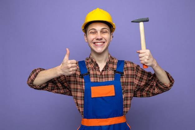 Jonge mannelijke bouwer die een uniforme hamer draagt die op een paarse muur wordt geïsoleerd