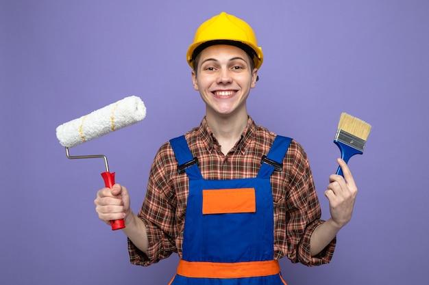 Jonge mannelijke bouwer die een uniforme kwast draagt met een rolborstel geïsoleerd op een paarse muur
