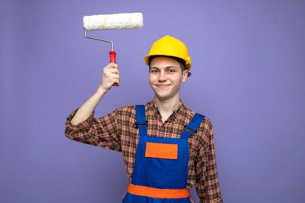 Jonge mannelijke bouwer die een uniforme rolborstel draagt die op een paarse muur wordt geïsoleerd