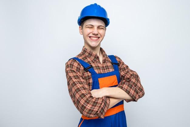Jonge mannelijke bouwer die uniform draagt dat op witte muur wordt geïsoleerd