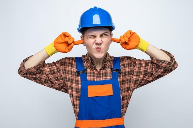 Jonge mannelijke bouwer die uniform draagt met handschoenen geïsoleerd op een witte muur