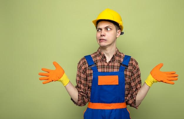 Jonge mannelijke bouwer die uniform draagt met handschoenen geïsoleerd op olijfgroene muur met kopieerruimte