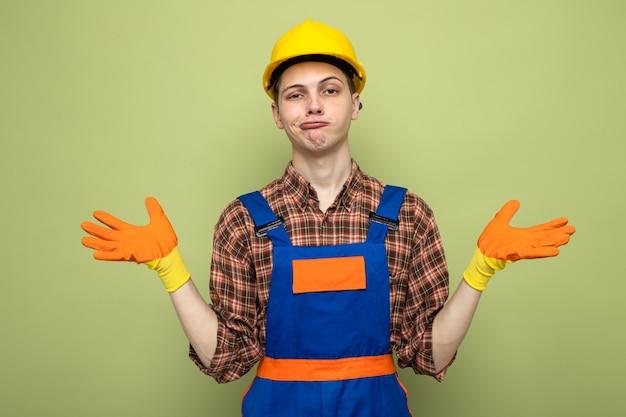 Jonge mannelijke bouwer die uniform draagt met handschoenen geïsoleerd op olijfgroene muur