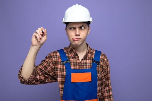 Jonge mannelijke bouwer die uniform vasthoudt en kijkt naar een marker geïsoleerd op een paarse muur
