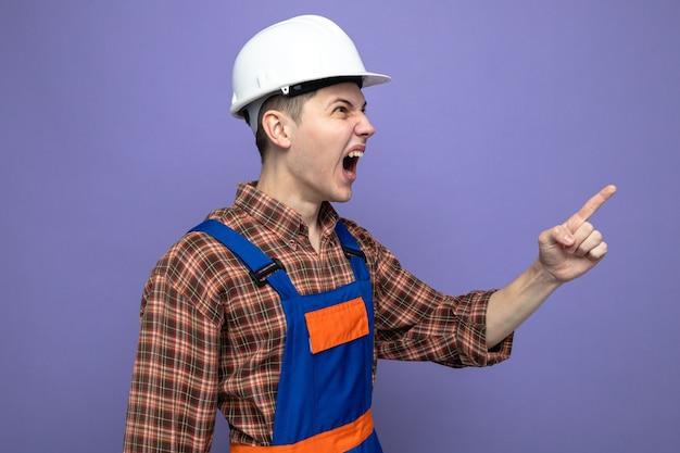 Jonge mannelijke bouwer draagt uniform geïsoleerd op paarse muur